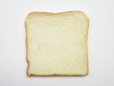 food stuff: Close-up image of one slice of white bread against the paper white background