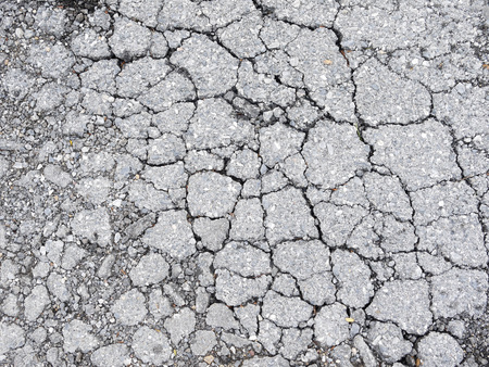 disintegrating: Macro closeup on concrete asphalt cracks on the road Stock Photo