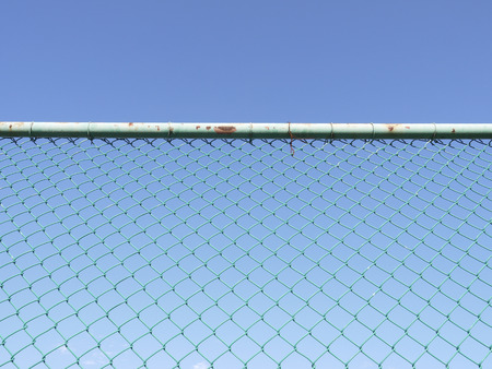 detain: Green seamless fence chain, Iron wire fence on blue sky background