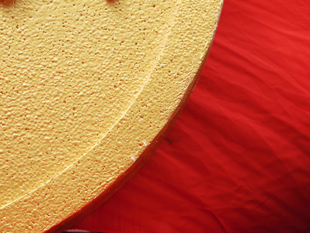 styrene: Gold plastic foam texture with red fabric cloth Stock Photo