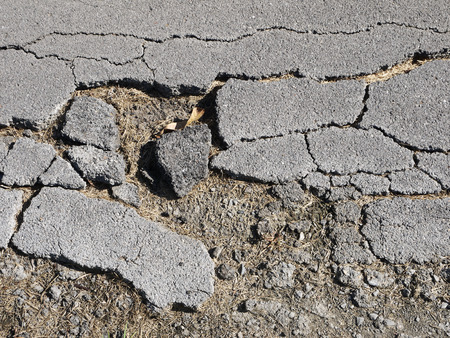 and worn out: Old worn and cracked asphalt with cracks