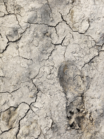 sump: footprint on the ground with crack Stock Photo