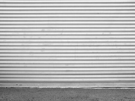 aluminum texture: ainted corrugated metal door with conrete wall and ground Stock Photo