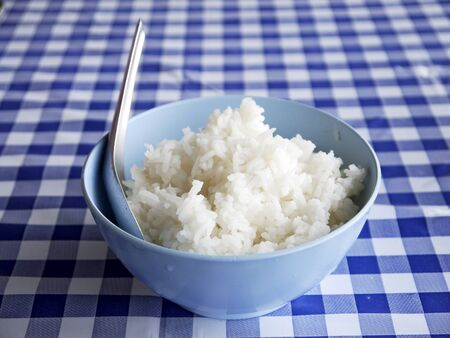grained: Rice in a cup on a table cloth Stock Photo