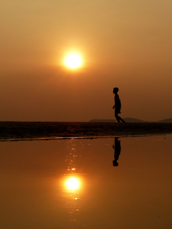 Silhouette boy walking on the beach at sunset