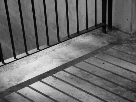 correctional facility: A closeup of view of a jail cells iron bars casting shadows on the prison floor with copy space