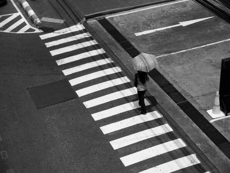 paso peatonal: Mujer con el paraguas de cruzar un paso de peatones de la calle Foto de archivo