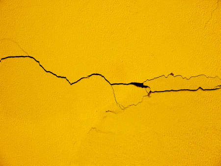 earthquake crack: yellow wall with crack texture Stock Photo