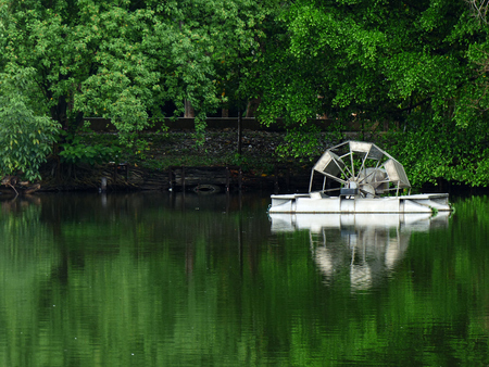 Metal water wheel floating on the lake of park Stock Photo
