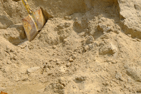 shovel in dirt: sand pile of construction