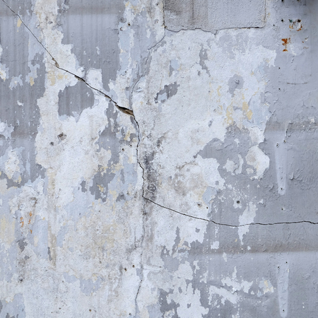 unevenly: old white wall with cracks
