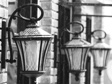 lit lamp: Black and white image of a brightly lit Lamp post against a textured brick wall Stock Photo