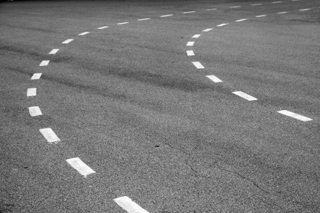marking up: Turning asphalt road with marking lines. Close up photo