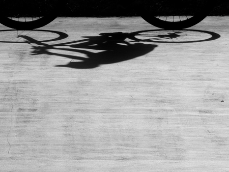 grey pattern: Black and white a bicycle against shadow on the street floor