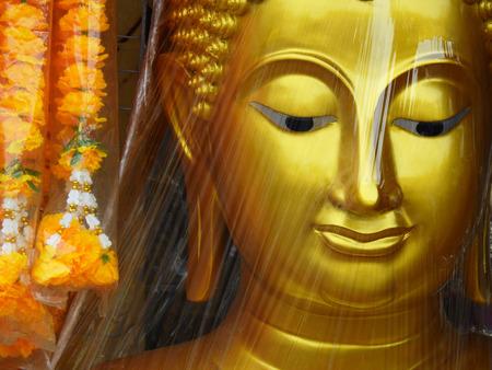 shroud: Plastic wrapped of gold face buddha statue Stock Photo
