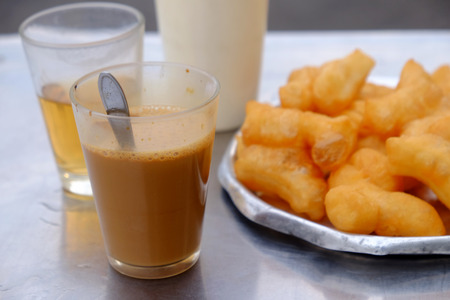 hot coffee in glass with deep-fried dough stick Imagens