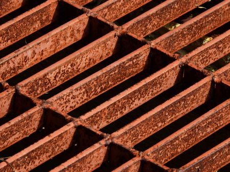 crack pipe: iron grating of drain with rust texture closeup Stock Photo