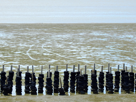 Poles and tires for the waves protection in wetlands Stock Photo