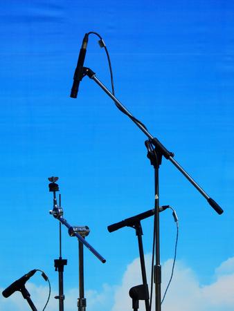 Mic stand on stage with blue background Reklamní fotografie