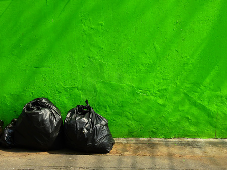 aged street green wall with pile of black garbage bag
