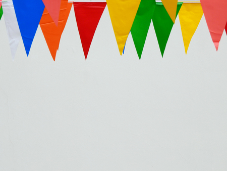 colorful flags festival hanging with white wall background Stock Photo