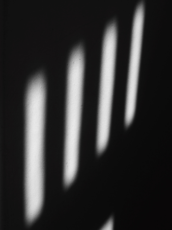 shadow on white wall with sunlight from window in the room