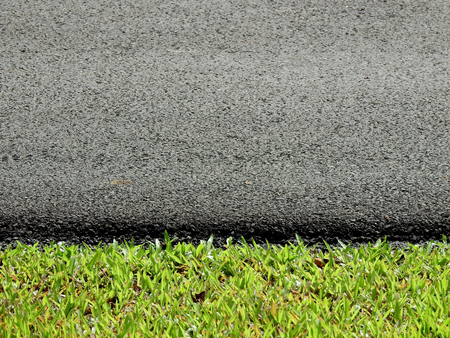 asphalt road with green grass lawn texture Stockfoto