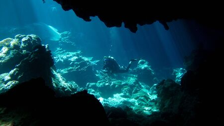 A diver in the distance exploring an underwater cavern.