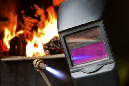 A welder holds up a cutting torch in front of a burning furnace