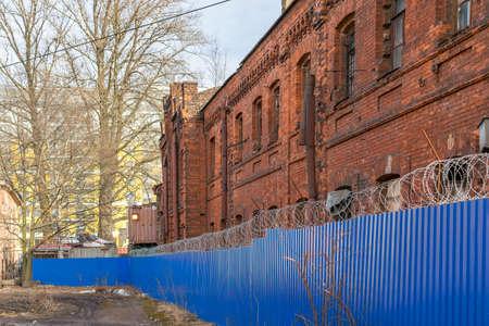 fil de fer: Le vieux bâtiment de briques derrière une clôture surmontée de barbelés Banque d'images