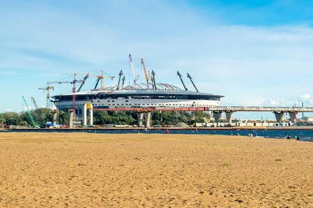 anniversary beach: SAINT PETERSBURG, RUSSIA - August, 2015: Park of the 300th anniversary of St. Petersburg. Beach. A view of the construction of a new football stadium on Krestovsky island