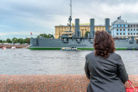 cruiser: Young girl admires the cruiser Aurora, the Neva River and the historic center of St. Petersburg