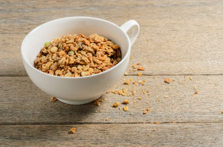 Muesli in a white bowl against the background of old village ash planks. Selective focus.