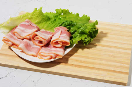 Rolled bacon slices are placed on a lettuce leaf on a plate. Bamboo cutting Board and texture table as background. Selective focus. Archivio Fotografico