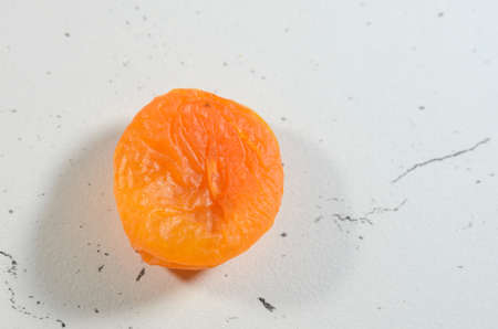 Berry of bright dried apricots on a background of textural black and white surface.