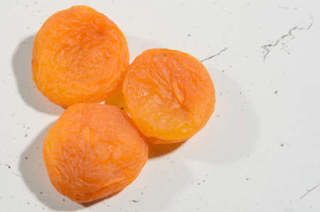 A few berries of bright dried apricots on a background of textural black and white surface.