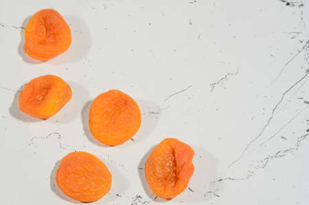 Five berries of bright dried apricots on a background of textural black and white surface. Reklamní fotografie
