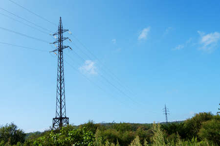 Electricity transmission. High-voltage power lines in the meadow. Stock Photo