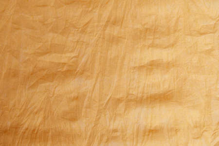 The texture of a crumpled yellow-gold disposable textile napkin. Stock fotó - 155452184
