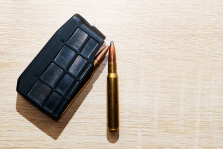 Hunting cartridges for a carbine on a wooden table surface. Selective focus. Stock fotó - 155452186