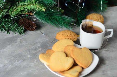 Homemade cookies in the shape of a heart in a white plate with a mug and a tea bag on the background of Christmas decorations. Selective focus.