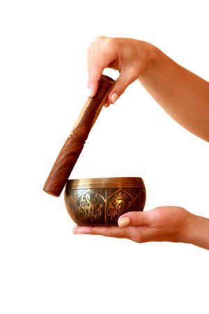 Tibetan Singing Bowl in womens hands on a white background