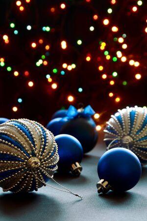 Blue Christmas balls on the background of lights Christmas tree garland.