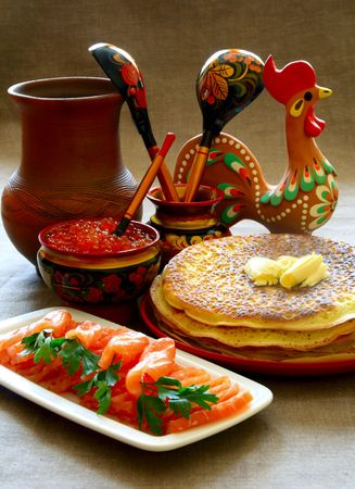 Salmon and caviar with pancakes in the Russian style with khokhloma dishes. Stock Photo