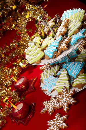 Christmas ginger cookies on a table decorated with tinsel and candles