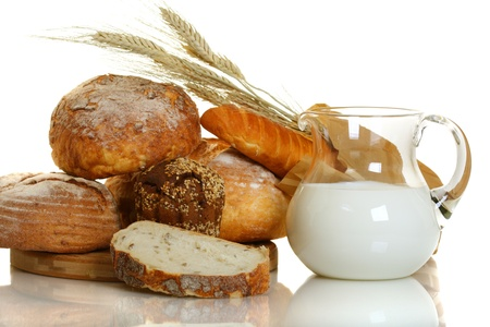 Fresh bread and milk in a glass jar on white background. photo