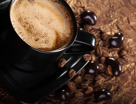 Coffee with milk, coffee beans and chocolate dragees. Stock Photo
