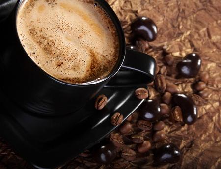 Kawa z mlekiem, ziaren kawy i czekoladowe dragees.