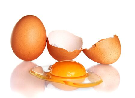 Hens egg and a broken egg yolk with a bright white background.