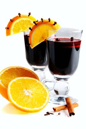 Mulled wine in glass, decorated with orange, cinnamon and clove isolated on a white background. Standard-Bild